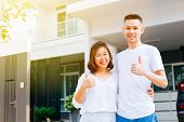 Asian Couple Standing In Front Of Their New House And Giving Thumbs Up. Newlyweds Family Just Moved poster
