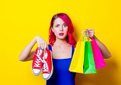 Young Pink Hair Girl In Blue Dress With Colored Shopping Bags And Gumshoes. Portrait Isolated On Yel poster