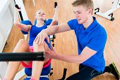 Female athlete and her physical therapist during exercise at workout equipment in health club poster