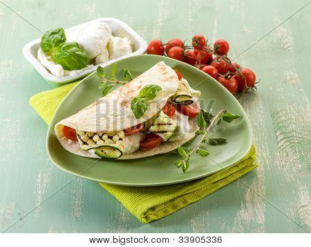 Piadina con mozzarella, grelled calabacines y tomates, típico italiano sandwich