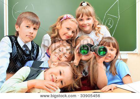 Happy schoolchildren at a classroom looking through binoculars. Education.