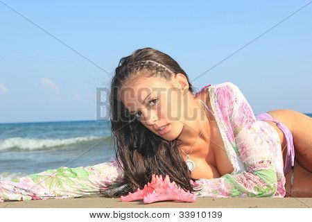Young woman on the beach enjoying the summertime