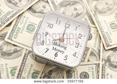Relógio com fazer dinheiro legenda sobre uma pilha de notas de cem dólares