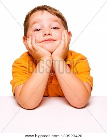Mischievous bored child sitting at desk