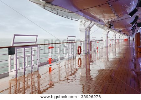Empty wet deck and railing of large cruise ship; thick fog over sea