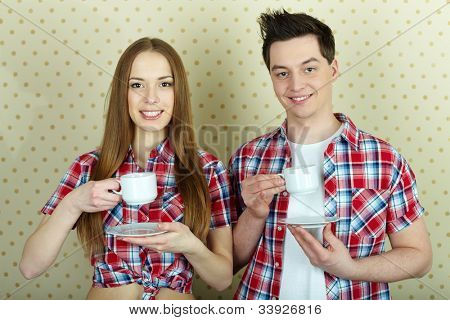 Young couple with cups and saucers looking at camera and smiling