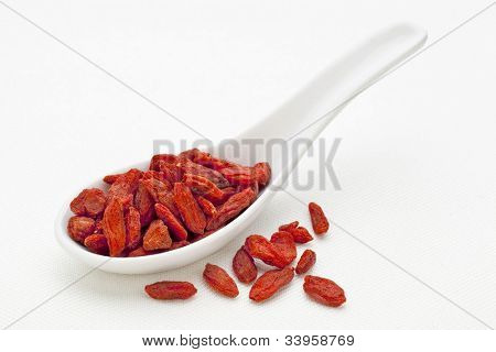 ceramic tablespoon of dried Tibetan goji berries (wolfberry) on  white canvas