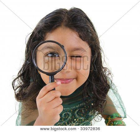 eine kleine Inderin Kollegen an der Kamera durch ein Vergrößerungsglas, isoliert auf weißem Hintergrund