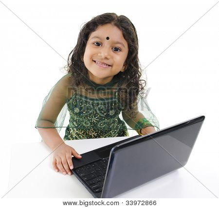 Little Indian girl using a laptop on table, isolated on white background