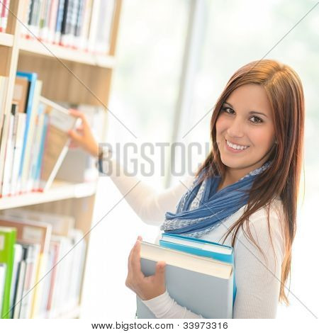 Smiling student choosing books from shelf library high school