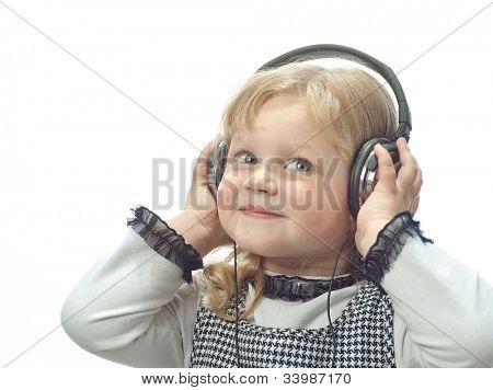 little child girl smiling isolated on white background with headphones leastening to music