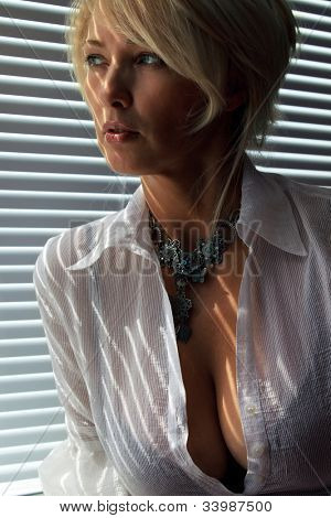 Blonde woman in the sunlight looking through jalousie