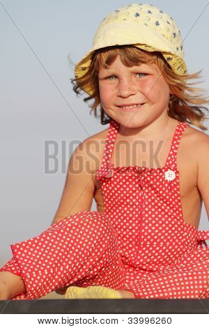 outdoor portrait of young happy girl in yellow summer hat isolated over blue sky