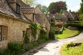 stock photo of old stone fence  - Traditional Cotswold cottages in England - JPG