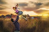 Father Throws Up His Daughter In Sunset Time. Child Fly In Sky. Fatherhood And Happy Childhood. Girl poster