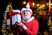 Present Box. New Year Holidays. Santa Claus Man Holds Christmas Gift Box. Bearded Man In Santa Hat H poster