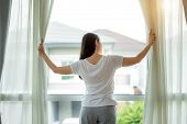 Rear View Of Asian Woman Waking Up In Her Bed Fully Rested Opening Window Curtains And Looking Throu poster