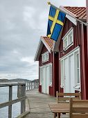 Swedish Flag Seaside. The Flag Of Sweden On A Small Beach Cottages In The Seaside Town Skärhamn. poster
