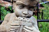pic of cherub  - Closeup of stone little cherub holding a musical instrument up to his lips - JPG