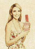 picture of olden days  - Faded And Textured Image Of A Vintage Woman With Smile Pop Corn And Movie Tickets In A Olden Day Drive In And Movie Theatre Concept - JPG