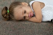 A Beautiful Little Girl Of European Appearance Blonde Hair Lying Sad On Street Asphalt. Childrens Pr poster