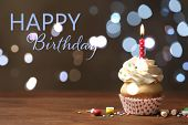 Delicious Cupcake With Candle On Wooden Table Against Blurred Lights. Happy Birthday poster