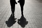 Two Women Walking Down The Street, Black Silhouettes And Shadows On Pavement. Female Couple On A Sid poster