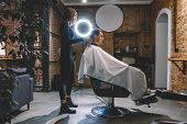 Beautiful Female Hairdresser Shaves The Head Of A Client Sitting In A Chair With An Electric Trimmer poster