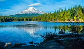 A Image Of Mt. Hood With A Reflection In A Lake, A Cloudy Sky, Across From A Picnic Bench. poster