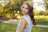 Beautiful Brown-haired Woman Looking At The Camera. A Teenager Walks In The Park At Sunset. Girl Wit poster