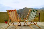 Pair Of Deck Chairs At The Veranda Against Beautiful Mountain View poster