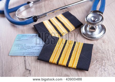 Close up of an airplane pilot's epaluetes with doctor's stethoscope and pilot certificate. Conceptual image of medical exam.