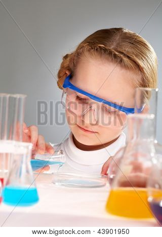 Vertical close-up of a curious young scientist pouring reagent into Petri dish