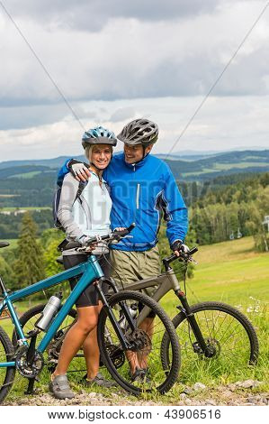 Young cuddling cyclists with mountain bikes during summer weekend