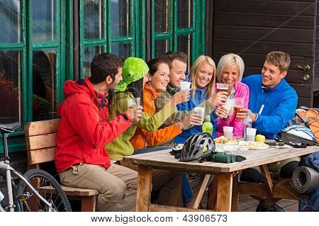 Happy young people resting and drinking beer after biking