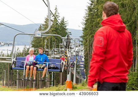 Young couple enjoying chair lift in the wood holiday resort