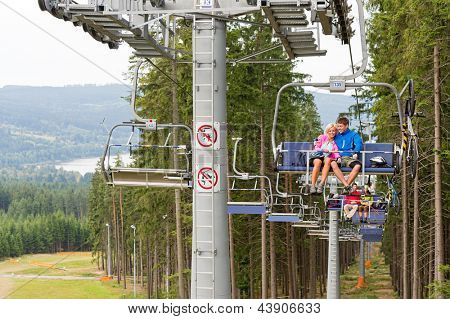Cuddling couple going through pinewood by chair lift