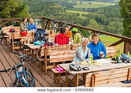 Young people relaxing looking at scenic mountain landscape  summer holiday