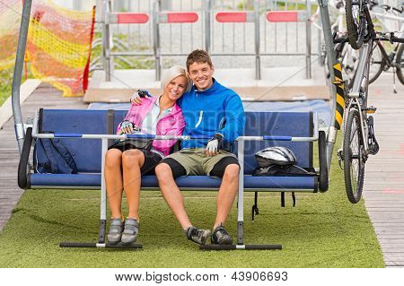 Cuddling happy couple sitting on chair lift with bicycles