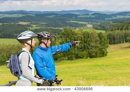 Sporty cyclist couple, man pointing to beautiful landscape