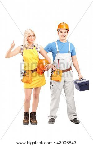 Full length portrait of a male and female construction workers with equipment isolated on white background