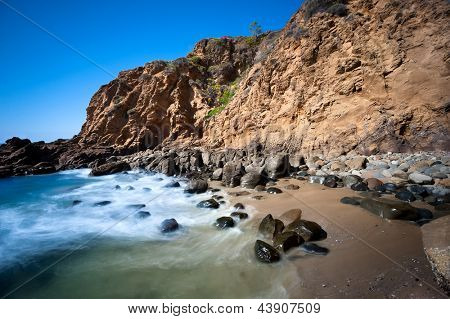 A secluded cover in Laguna Beach, California shows the seawater rushing to shore over smooth boulders.