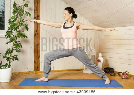 An image of a pretty woman doing yoga at home - Virabhadrasana