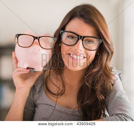 Young Woman Holding Piggy Bank Wearing Glasses, Indoors