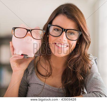 Jovem mulher exploração cofrinho usando óculos, dentro de casa
