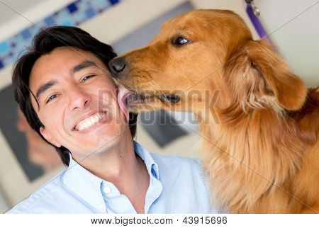 Golden retriever licking his owner in the face as a sign of affection