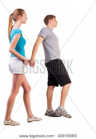 Back view of going young couple walking beautiful friendly girl and guy in shorts together. Rear view people collection.   backside view of person.  Isolated over white background.