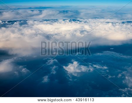 clouds. view from window of an airplane flying in clouds. top view. waves of clouds form a real storm