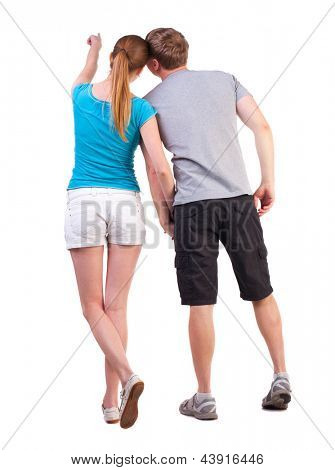 Back view of young couple pointing. Rear view people collection. backside view person.  Isolated over white background. blonde teen shows her boyfriend at something in the distance, holding his hand