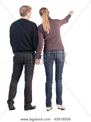 Back view of young couple (man and woman) hug and pointing. beautiful friendly girl and guy together. Rear view. Isolated over white background. wife says to her husband that the important